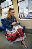 Passenger with an iconic telephone box skirt on a DLR train, Canary Wharf, London - Jess Hurd - 2010s,2017,apparel,box,boxes,British,BT,Canary Wharf,carriage,carriages,CELLULAR,cities,City,clothes,clothing,communicating,communication,DLR train,female,holiday,holiday maker,holiday makers,holidaym