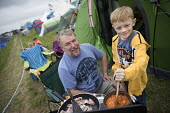 Camping breakfast, Tolpuddle Martyrs Festival, Dorset. - Jess Hurd - 2010s,2017,ACE,boy,boys,breakfast,camp,Camping,Camping Site,camps,campsite,child,CHILDHOOD,children,COOKERY,cooking,cooking utensils,DAD,DADDIES,DADDY,DADS,Dorset,families,family,father,FATHERHOOD,fat