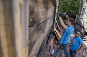 Detroit, Michigan, USA Volunteers in a community improvement project called Life Remodeled workers from Fiat Chrysler Automobiles (FCA) boarding up an abandoned house - Jim West - 01-08-2017