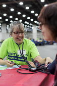 Detroit, Michigan, USA A volunteer nurse taking the blood pressure of a patient, Motor City Medical Mission, a free three day medical clinic sponsored by the Adventist Medical Evangelism Network - Jim West - 09-08-2017