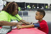 Detroit, Michigan, USA A volunteer nurse taking the blood pressure of a patient, Motor City Medical Mission, a free three day medical clinic sponsored by the Adventist Medical Evangelism Network - Jim West - 2010s,2017,Adventist Medical Evangelism Network,African American,African Americans,America,BAME,BAMEs,Belief,black,blood,blood pressure,BME,bmes,boy,boys,care,charitable,charity,check,checking,child,C