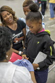 Detroit, Michigan, USA A volunteer nurse checking the blood sugar of a child, Motor City Medical Mission, a free three day medical clinic sponsored by the Adventist Medical Evangelism Network - Jim West - 09-08-2017