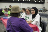 Detroit, Michigan USA Volunteer nurse practitioners from Eastern Michigan University talking to a patient, Motor City Medical Mission, a free three day medical clinic sponsored by the Adventist Medica... - Jim West - 09-08-2017