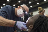 Detroit, Michigan USA A volunteer dental hygenist examining the teeth of a patient, Motor City Medical Mission, a free three day medical clinic sponsored by the Adventist Medical Evangelism Network - Jim West - 2010s,2017,Adventist Medical Evangelism Network,African American,African Americans,America,BAME,BAMEs,Belief,black,BME,bmes,care,charitable,charity,christian,christianity,christians,clinic,clinics,con
