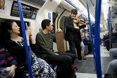 Homeless musician entertaining commuters on the Northern line with his rendition of Mozart, London underground - Jess Hurd - 2010s,2017,ACE,adult,adults,age,ageing population,Arts,baggar,beg,beggar,beggars,BEGGER,begging,begs,busker,buskers,busking,carriage,carriages,cities,City,COMMUTE,commuter,commuters,commuting,Culture,