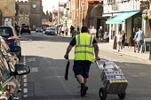 Driver making a delivery of cans of drinks to a shop in the High Street, Stratford upon Avon, Warwickshire - John Harris - 2010s,2017,can,cans,cart,carts,cross,Crossing The Road,deliveries,delivering,delivery,driver,drivers,DRIVING,EBF,Economic,Economy,employee,employees,Employment,food,FOODS,High St,High Street,job,jobs,