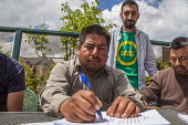 Burlington, Washington, USA Members of Familias Unidas por la Justicia signing a contract negotiated with Sakuma Brothers Farms, with Danny Weeden, general manager of the company, after four years of... - David Bacon - 2010s,2017,ACTIVIST,ACTIVISTS,against,agreement,AGREEMENTS,american,americans,amerindian,amerindians,BAME,BAMEs,berry,blueberry,BME,bmes,boss,bosses,Brothers,CAMPAIGN,campaigner,campaigners,CAMPAIGNIN