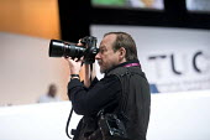 Photographer John Harris working at TUC Congress, Brighton 2017 - Jess Hurd - 2010s,2017,Brighton,camera,cameras,Conference,conferences,Congress,employee,employees,Employment,job,jobs,John Harris,LBR,media,member,member members,members,older,people,Photographer,photographers,ph