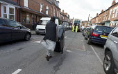 Bin workers strike. Resident pursuing refuse collection by contractors with his wheelie bin, Sparkbrook, Birmingham. Strike is costing 40,000 pounds a day. The Labour council have issued redundancies... - John Harris - 2010s,2017,Asian,Asians,BAME,BAMEs,Black,BME,bmes,cities,City,collection,collector,collectors,contractor,contractors,council,disputes,diversity,employee,employees,Employment,ethnic,ethnicity,industria