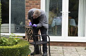 Forensic scene of crime investigator dusting for fingerprints and searching for clues after an attempted break in to a house, Warwickshire. The burglars were disturbed whilst smashing double glazed wi... - John Harris - 2010s,2017,break,Break in,broken,brush,brushes,burglar,burglars,burglary,CLJ,clue,clues,Crime,crime scene investigation,CSI,damage,damaged,double glazing,EGT,employee,employees,Employment,Evidence Gat
