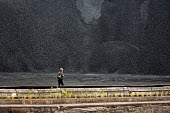 Sault Ste. Marie, Ontario Canada - A worker walks past a pile of coal at the Algoma steel mill on the shore of the St. Marys River. - Jim West - 05-09-2017