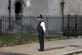 A lone police officer on duty in Westminster, London - Stefano Cagnoni - 2010s,2017,adult,adults,autumn leaves,CLJ,constable,employee,employees,Employment,force,guard,guarding,guards,handcuffs,job,jobs,law,LBR,London,Metropolitan Police Service,officer,officers,patrol,patr