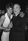 Gene Kelly guest of honour at a Variety Club lunch. With dancer and actress Suzanne Danielle, London 1980 - NLA - 1980,1980s,ACE,Arts,celebrities,celebrity,Culture,FEMALE,Gene Kelly,holding hands,Leisure,LFL,LIFE,Lifestyle,London,male,man,men,PEOPLE,person,persons,RECREATION,RECREATIONAL,Susan Danielle,Variety Cl