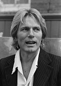Singer Adam Faith promoting the vehicle seat belt, London, 1980. He was seriously injured in a car crash in 1973. A law making seat belts compulsory was introduced in January 1983 - NLA - 1980,1980s,accident,accidental,accidents,Adam Faith,AUTO,AUTOMOBILE,AUTOMOBILES,AUTOMOTIVE,car,cars,cities,City,crash,crashed,DIA,incident,incidents,injured,INJURIES,INJURY,London,making,male,man,men,