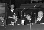 Tiny Rowland speaking with Edward du Cann (2nd R) Lonrho shareholders meeting, London, 1973. Edward Heath described Lonrho as The unacceptbale face of capitalism - Peter Arkell - 1970s,1973,capitalism,capitalist,EBF,Economic,Economy,Edward du Cann,London,Lonrho,male,man,meeting,MEETINGS,men,people,person,persons,SPEAKER,SPEAKERS,speaking,SPEECH,Tiny Rowland