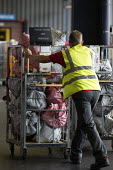 Swansea Mail Centre, Wales - John Harris - 2010s,2017,bag,bags,bays,by hand,cart,carts,communicating,communication,letter,letters,loading bay,Logistics Services,mail,male,man,manual,men,people,person,persons,Postal Service,public services,push