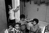 1973 Damp and overcrowded housing, Richardson House, Haggerston Estate, East London. Sheila Kennedy pointing to problems in her house, with her 4 children - NLA - 1970s,1973,adult,adults,BAME,BAMEs,BEMM,BEMMS,Black,Black and White,BME,bmes,boy,boys,brother,brothers,child,CHILDHOOD,children,cities,City,Council Housing,Council Housing,damp,damp housing,diversity,