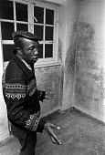 1973 Damp and poor housing, Richardson House, Haggerston Estate, East London, a tenant showing the damp - NLA - 1970s,1973,BAME,BAMEs,Black,BME,bmes,cities,City,Council Housing,Council Housing,damp,damp housing,diversity,ethnic,ethnicity,excluded,exclusion,HARDSHIP,House,houses,Housing,Housing Estate,impoverish