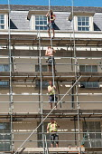 Construction workers erecting scaffolding on an apartment block, Richmond, London - Philip Wolmuth - builders, building, construction,2010s,2017,apartment,BUILDER,builders,building,Building Worker,building workers,buildings,cities,City,construction,Construction Industry,EBF,Economic,Economy,employee,