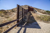 Tecate, California, USA An old section of the US Mexican border made from an old aircraft landing strip and a well worn path crossing the border - David Bacon - 28-10-2017