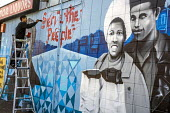 Oakland, California, USA, Artists painting the Black Panther Mural on the wall of a liquor store, celebrating the history of the Black Panther Party. The mural is a portrait of Huey P. Newton, party c... - David Bacon - African Americans,2010s,2017,ACE,adult,adults,aerosol,aerosols,African,African American,American,americans,art,artist,artists,arts,artwork,artworks,BAME,BAMEs,Black,Black Panther,Black Panthers,BME,bm
