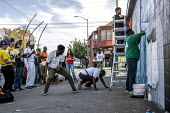 Oakland, California, USA, local capoeira group performing on the sidewalk while artists paint a Black Panther Mural on the wall of a liquor store, celebrating the history of the Black Panther Party. T... - David Bacon - 23-10-2017