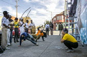 Oakland, California, USA, local capoeira group performing on the sidewalk while artists paint a Black Panther Mural on the wall of a liquor store, celebrating the history of the Black Panther Party. T... - David Bacon - African Americans,2010s,2017,ACE,adult,adults,African,African American,American,americans,art,artist,artists,arts,artwork,artworks,BAME,BAMEs,Black,Black Panther,Black Panthers,BME,bmes,BPP,Brazil,Cal