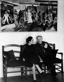 Artist Marc Chagall talking with his second wife Valentine sitting below The Wedding a 1910 Chagall painting, Vence, France 1961 - Felix H. Man - 1960s,1961,ACE art,art,artist,artists,artwork,artworks,communicating,communication,conversation,conversations,culture,dialogue,discourse,discuss,discusses,discussing,discussion,EMOTION,EMOTIONAL,EMOTI