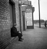 Easington 1948 retired miner resting on a step by The Empire cinema with advertisments for local film screenings - Elisabeth Chat - 01-06-1948