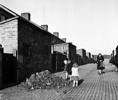 Miners children playing with coal, back streets, Easington 1948 - Elisabeth Chat - 1940s,1948,boy,boys,boys and girls,capitalism,capitalist,child,CHILDHOOD,children,coal,Coal Industry,Coal Mine,coalfield,coalindustry,collieries,colliery,County Durham,excluded,exclusion,female,female