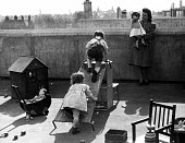 Children on a London rooftop playground, 1948 playing together under supervision while daily life goes on in the streets beneath them in post war Britain - Elisabeth Chat - 1940s,1948,areas,boy,boys,CARE,carer,carers,child,child care,child carer,child carers,childcare,CHILD-CARE,CHILDHOOD,CHILDMINDING,children,cities,city,CRECH,creche,creches,day care,daycare,doll,EARLY,