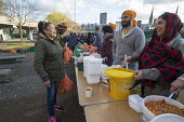Homeless and hungry queuing for food, Coventry. The soup kitchen and food bank is provided by The Midland Langar Seva Society - John Harris - 2010s,2017,Asian,Asians,assisting,BAME,BAMEs,bank,BANKS,Belief,Black,BME,bmes,charitable,charity,cities,City,conviction,curry,diversity,ethnic,ethnicity,excluded,exclusion,faith,FEMALE,food,food aid d