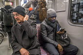 Passengers on a Berlin underground train or U-Bahn, Germany - David Bacon - 2010s,2017,adult,adults,age,ageing population,BAME,BAMEs,Berlin,Black,Black and White,BME,bmes,bored,boredom,boring,call,calls,carriage,carriages,CELLULAR,cities,city,communicating,communication,COMMU