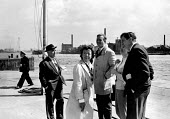 London 1961 Director Joan Littlewood with Theatre Workshop cast of Sparrers Cant Sing researching location shots at Stepney Riverside for a film to be made of the same production. Actor Stephen Lewis... - Alex Low - 1960s,1961,ACE,ACTING,actor,actors,adult,adults,Arts,cities,City,Culture,director,directors,drama,DRAMATIC,FEMALE,Joan Littlewood,London,male,man,MATURE,men,people,person,persons,play,playing,plays,ri