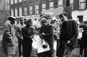 1959 The Golden City Dixies from Pretoria, South Africa buying flowers from a licensed street trader, central London - Alan Vines - 1950s,1959,Africa,BAME,BAMEs,barrow,black,BME,bmes,bouquet of flowers,Bunch of Flowers,business,buy,buyer,buyers,buying,cities,City,commerce,commodities,commodity,diversity,EBF,Economic,Economy,ethnic