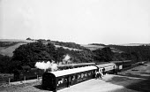 Devon 1959 Steam train passes by holidaymakers talking outside their Camping Coaches, disused train carriages converted for holiday use in Loddiswell near Kingsbridge - Alan Vines - 13-08-1959