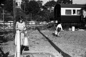 Devon 1959 children on summer holiday collecting water from a standpipe outside their Camping Coach holiday home, disused train carriages converted for holiday use Loddiswell near Kingsbridge - Alan Vines - 13-08-1959