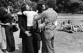 Homosexual men kissing in public thereby technically committing an illegal act, St James Park, London 1975 Campaigning for reform of the Law - Chris Davies - 1970s,1975,activist,activists,against,age of consent,anti gay,antigay,campaign,Campaign for Homosexual Equality,campaigner,campaigners,campaigning,CAMPAIGNS,CHE,cities,City,DEMONSTRATING,Demonstration
