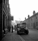 Men standing outside Ministry of Labour and National Service, Warrington 1949 - Elisabeth Chat - 1940s,1949,AUTO,AUTOMOBILE,AUTOMOBILES,AUTOMOTIVE,car,cars,chimney,CHIMNEYS,cobbled street,cobbles,employee,employees,Employment,industrial town,job,jobless,jobs,jobseeker,jobseekers,LBR,male,man,Marg