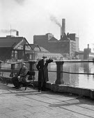Men on bridge whistling, Bishops Wharf Tannery Warrington 1949 - Elisabeth Chat - 1940s,1949,bridge,bridges,canal,canals,capitalism,capitalist,chimney,CHIMNEYS,EBF,Economic,Economy,industrial town,Industries,industry,jobless,jobseeker,jobseekers,maker,makers,making,male,man,man whi