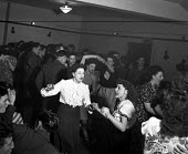 1949 Off duty Americans from Burtonwood USAAF dancing with local women, The Broadway Club, Warrington. The airbase was reopened to support the Cold War effort through the maintenance and overhaul of a... - Elisabeth Chat - 1940s,1949,ACE,aircraft,airforce,airman,airmen,Armed Forces,club,clubs,culture,dance,dance hall,dancer,dancers,dancing,dress,EMOTION,EMOTIONAL,EMOTIONS,enjoying,enjoyment,fashion,FEMALE,fun,HAPPINESS,