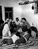 Post war UN World Health Organisation programme Bosnia 1948. Family of Hassan Bajraktavevic listening to UN Health worker talking to them about hygiene and advice for prevention of illness - Eric Schwab - 1940s,1948,adult,adults,advice,ADVISE,advising,Aid Agency,attention,attentive,barefeet,barefoot,Bosnia,care,child,CHILDHOOD,children,communicating,communication,communities,community,congenital,conver