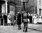 Photographers taking photographs at two different weddings 1965 black and white, Brixton Registry Office London, competing for space to take photos of their respective bride and groom - Malcolm Aird - 03-08-1965