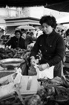 Street vendor selling fruit and vegetables, street market Rome 1976 - Mike Sheridan - 1970s,1976,bought,buy,buyer,buyers,buying,cities,City,commerce,commodities,commodity,consumer,consumers,customer,customers,EARNINGS,EBF,EBF economy,Economic,Economy,employee,employees,Employment,FEMAL