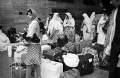 Asian migrant workers arriving at Rome railway station 1976 - Mike Sheridan - 1970s,1976,arrival,arrivals,arrive,arrived,arrives,arriving,Asian,Asians,bag,baggage,bags,BAME,BAMEs,Black,BME,bmes,cities,City,Diaspora,diversity,dress,EBF,EBF economy,Economic,economic migrants,Econ