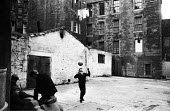 Edinburgh 1965 boys playing football in a run down space at the back of the Traverse Theatre, Lawnmarket. The small radical arts venue was once a doss house and brothel known as Kellys Paradise and He... - Patrick Eagar - 1960s,1965,ACE,Arts,boy,boys,child,CHILDHOOD,children,cities,City,Culture,excluded,exclusion,Festival,festivals,football,HARDSHIP,heading,impoverished,impoverishment,INEQUALITY,juvenile,juveniles,kid,