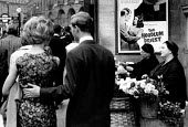 Flower sellers, Piccadilly London 1961 by a poster for The Hoodlum Priest film - Romano Cagnoni - 11-04-1961
