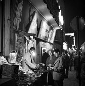 Paris 1961 street market at night - Romano Cagnoni - 1960s,1961,adult,adults,cities,City,couple,COUPLES,France,French,leisure,LFL,LIFE,lifestyle,light,male,man,market,MATURE,men,night,night time,Paris,people,person,persons,RECREATION,RECREATIONAL,street