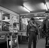 Young men hanging around in an amusement arcade at night Paris 1961 - Romano Cagnoni - 13-05-1961