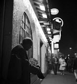 Man begging with his cap in hand, Paris street at night 1961 - Romano Cagnoni - 1960s,1961,baggar,beg,beggar,beggars,BEGGER,begging,begs,cities,City,excluded,exclusion,France,French,HARDSHIP,impoverished,impoverishment,INEQUALITY,leisure,LFL,LIFE,lifestyle,light,male,man,Marginal